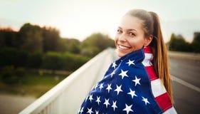 Härlig kvinna som slås in i amerikanska flaggan arkivfoto