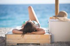 Härlig kvinna som solbadar i en bikini på en strand på den tropiska loppsemesterorten Arkivfoto
