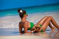 Härlig kvinna som solbadar på en strand med kokosnötcoctailen Royaltyfria Bilder