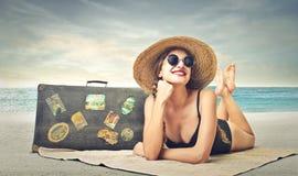 Härlig kvinna som solbadar på stranden Arkivbild