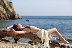 Härlig kvinna som solbadar på stranden på semestrar Arkivbilder