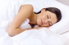 Härlig kvinna som sover i säng Arkivfoto