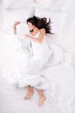 Härlig kvinna som sover och kramar snowboarden Royaltyfri Foto