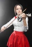 Härlig kvinna som spelar fiolen på en svart bakgrund Royaltyfri Bild