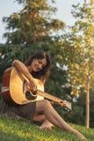 Härlig kvinna som spelar gitarren i parkera arkivfoto