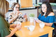 Härlig kvinna som spelar kort med vänner royaltyfri fotografi