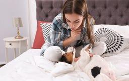 Härlig kvinna som spelar med hennes hund i säng royaltyfri foto