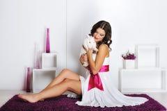 Härlig kvinna som spelar med kanin Arkivbild