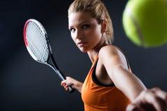 Härlig kvinna som spelar tennis inomhus Isolerat på svart royaltyfri bild