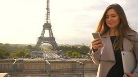 Härlig kvinna som står den near Eiffeltorn med bärbara datorn och smartphonen arkivfilmer