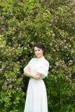 Härlig kvinna som står nära blommande äppleträd fotografering för bildbyråer