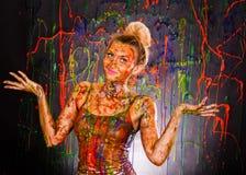 Härlig kvinna som täckas med mångfärgade målarfärger royaltyfri foto