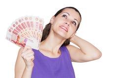 Härlig kvinna som tänker hur man spenderar pengarna Arkivbild