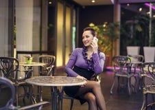Härlig kvinna som talar på telefonen i coffee shop Arkivfoto