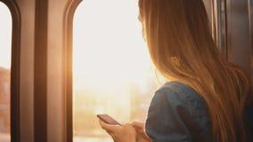 Härlig kvinna som tar en gångtunnel i Chicago, USA Attraktiv kvinnlig användande smartphone, medan drevet är rörande på solnedgån arkivfilmer