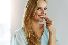 Härlig kvinna som tar preventivpilleren, medicin tillägg vitaminer Arkivfoto