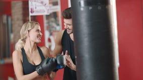 Härlig kvinna som tillsammans boxas stridpåsen med sportinstruktören lager videofilmer
