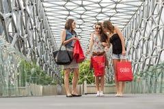Härlig kvinna som tre går på bron, shoppade de, shoppingpåsen i hans hand fotografering för bildbyråer
