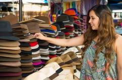 Härlig kvinna som trycker på en handgjord Panama hatt på hantverkmarknaden i Otavalo, Ecuador, färgrik tygbakgrund fotografering för bildbyråer