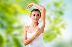 Härlig kvinna som trycker på hennes armhåla vid fjädern fotografering för bildbyråer