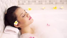 Härlig kvinna som tycker om brunnsorten i badkar lager videofilmer