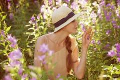Härlig kvinna som tycker om doften av vildblommor Arkivfoto