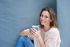 Härlig kvinna som tycker om en drink av ett kaffe arkivbild