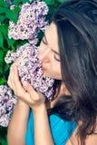 Härlig kvinna som tycker om lukten av blommor Royaltyfria Bilder