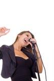Härlig kvinna som tycker om musik som sjunger på mikrofonen Arkivfoton
