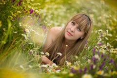 Härlig kvinna som tycker om tusenskönafältet, trevlig kvinnlig som ner ligger i ängen av blommor, nätt koppla av för flicka som ä Royaltyfria Bilder