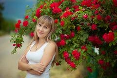 Härlig kvinna som tycker om tusenskönafältet, trevlig kvinnlig som ner ligger i ängen av blommor, nätt koppla av för flicka som ä Royaltyfri Foto
