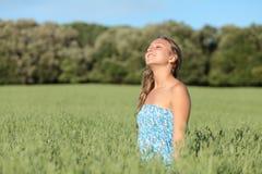Härlig kvinna som tycker om vinden i en grön äng Arkivbild