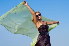 Härlig kvinna som upp rymmer en grön scarf Royaltyfri Bild