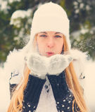 Härlig kvinna som utomhus blåser snö Arkivbild