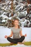 Härlig kvinna som utomhus gör yoga i snö arkivbilder