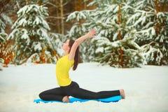 Härlig kvinna som utomhus gör yoga i snön Royaltyfri Foto