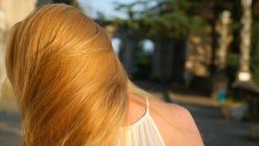 Härlig kvinna som utomhus utformar hår Toppen ultrarapid Lycklig lugna flicka med långt hår och att ha gyckel i parkera stock video