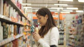 Härlig kvinna som väljer kroppomsorgprodukter i supermarket lager videofilmer