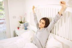Härlig kvinna som vaknar upp i säng i morgonen som sträcker det avkopplade sned bollskottet Royaltyfri Fotografi