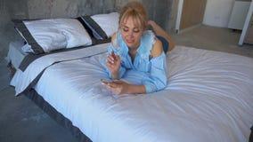 Härlig kvinna som vilar och talar på telefonen som ligger på dubbelsäng i sovrum med gråa väggar stock video