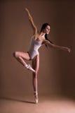 Härlig kvinnabalettdansör som dansar över beiga royaltyfri foto