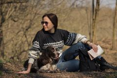 Härlig kvinnabrunett och bruntcockerspaniel i skogen Arkivbild