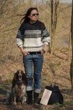 Härlig kvinnabrunett och bruntcockerspaniel i skogen Arkivfoton