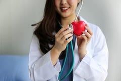 Härlig kvinnadoktor med stetoskopet som rymmer hjärta royaltyfri fotografi