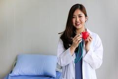 Härlig kvinnadoktor med stetoskopet som rymmer hjärta royaltyfria foton