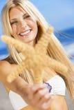 Härlig kvinnaflicka i bikini med sjöstjärnan på stranden Royaltyfria Foton