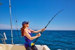 Härlig kvinnaflickametspö som fiska med drag i i fartyg Arkivfoto