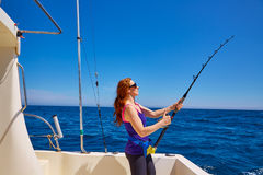 Härlig kvinnaflickametspö som fiska med drag i i fartyg Royaltyfria Bilder
