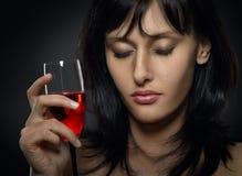 Härlig kvinnagråt med ett exponeringsglas av rött vin Arkivfoto