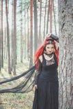 Härlig kvinnahäxa med rött hår i skogen Arkivfoto